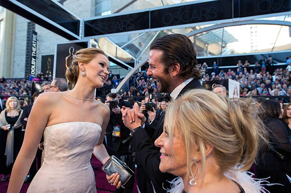 Jennifer Lawrence, Oscar-nominee for Actress in a Leading Role, and Bradley Cooper, Oscar-nominee for Actor in a Leading Role arrive for The Oscars at the Dolby Theatre in Hollywood, California on Feb. 24, 2013. Also pictured: Cooper's mother, Glo