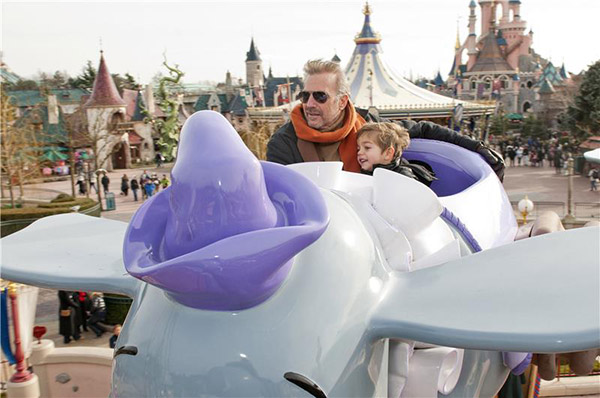 Kevin Costner takes his son on the Dumbo ride at Disneyland Paris on Feb. 3, 2013. He and his wife visited the park with their three children.
