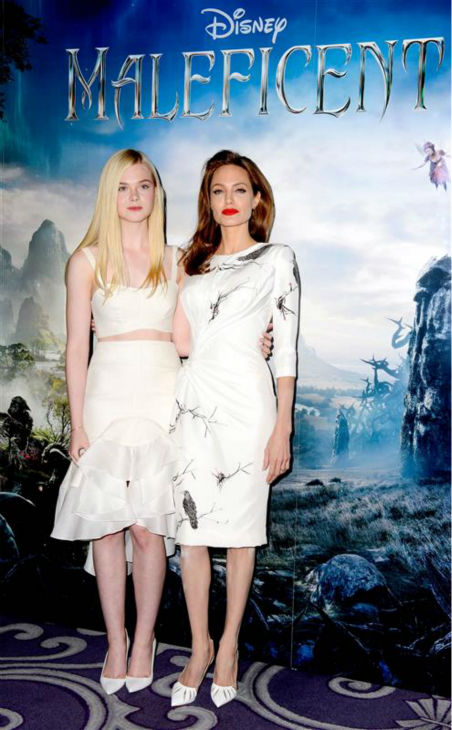 Elle Fanning and co-star Angelina Jolie appear at a photo call for &#39;Maleficent&#39; in London on May 9, 2014. Fanning is wearing an Ellery Fall 2014 crop top and high-waist, ruffled, asymmetrical, knee-length skirt. Jolie is wearing a raven-print dress by Atelier Versace. <span class=meta>(Richard Young &#47; REX &#47; Startraksphoto.com)</span>