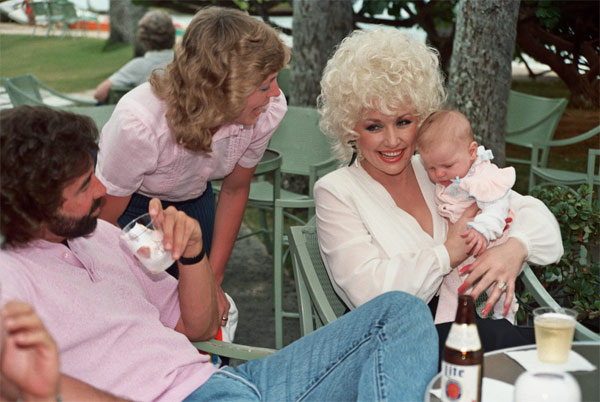 Alan Light describes this photo, which he says was taken in Hawaii: 'Dolly Parton holds my niece Amy as my sister Jan looks on. Photo taken at the Kahala Hilton Hotel, May 1984.'