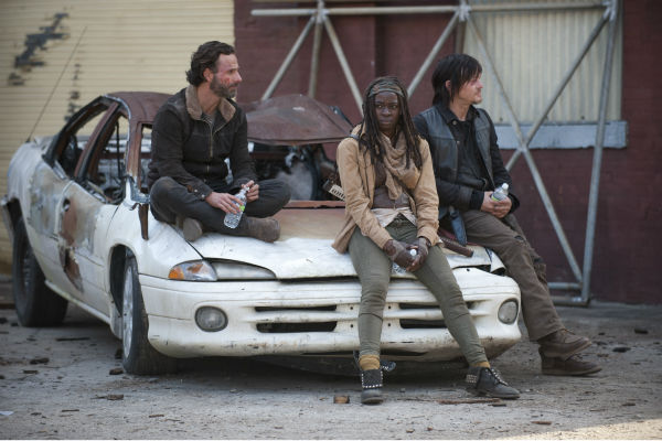 "<div class=""meta ""><span class=""caption-text "">Andrew Lincoln (Rick Grimes), Danai Gurira (Michonne) and Norman Reedus (Daryl Dixon) hang out on a car on the set of AMC's 'The Walking Dead' season 4 finale, which aired on March 30, 2014. (Gene Page / AMC)</span></div>"