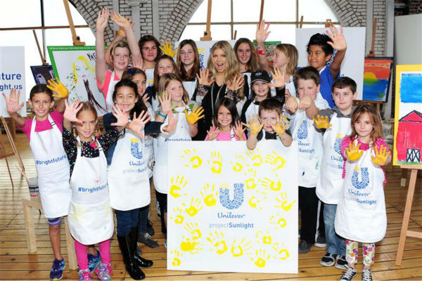 Fergie poses with children at a Solar Studios in Glendale, California on Nov. 20, 2013. The singer teamed up with Unilever on Universal Children's Day to launch the new global program Unilever Project Sunlight.