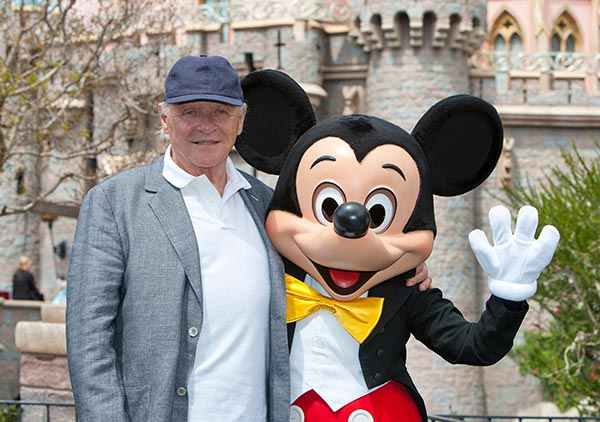 Sir Anthony Hopkins meets Mickey Mouse in front of Sleeping Beauty Castle at Disneyland park in Anaheim, California, on Monday, April 1, 2013.