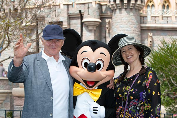 Sir Anthony Hopkins and wife Stella Arroyave meet Mickey Mouse in front of Sleeping Beauty Castle at Disneyland park in Anaheim, California, on Monday, April 1, 2013.