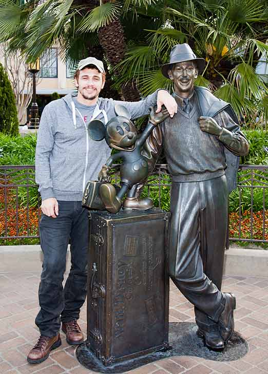 James Franco poses with a bronze statue of a young Walt Disney and his most famous creation, Mickey Mouse, called 'Storytellers,' at Disney's California Adventure park in Anaheim, California on Thursday, March 28, 2013.