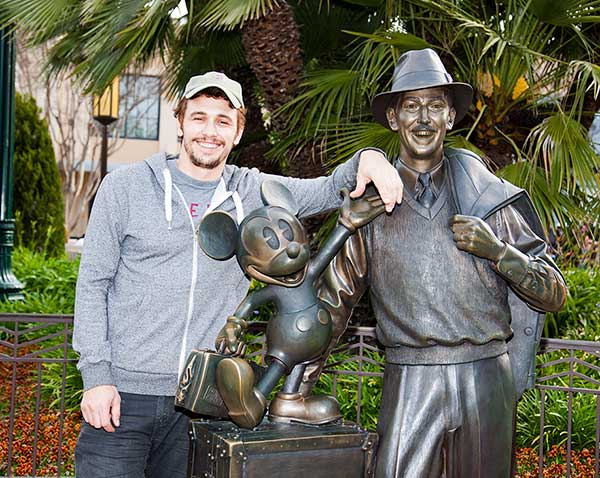 James Franco poses with a bronze statue of a...