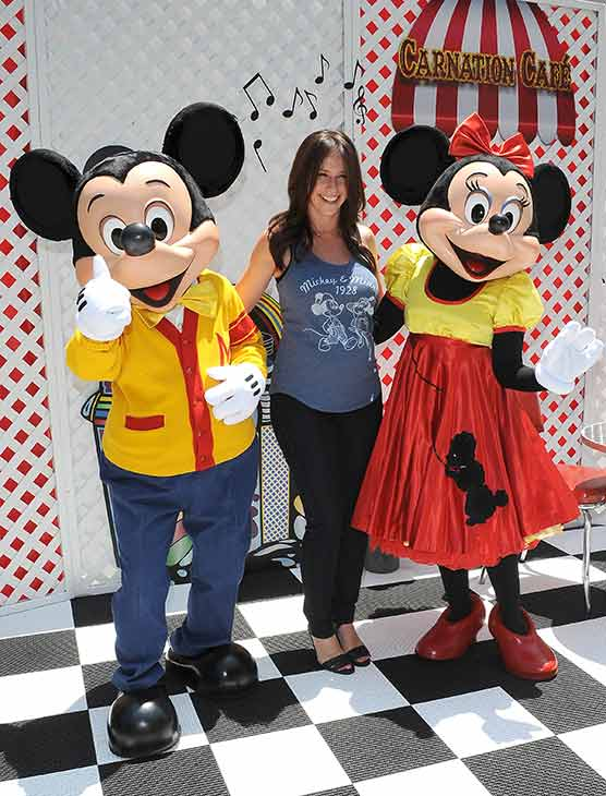 A pregnant Jennifer Love Hewitt poses with Mickey and Minnie Mouse at Old Navy's Mickey Through The Decades Collection Launch at the Walt Disney Company studio lot in Burbank, California.