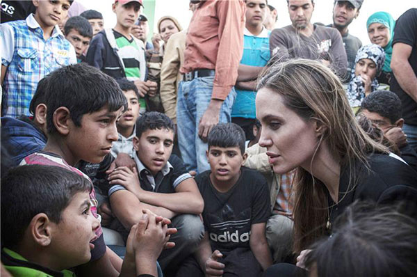 Angelina Jolie speaks to Syrian refugees who have taken shelter at a Jordanian military camp on the Jordan-Syria border on June 18, 2013.