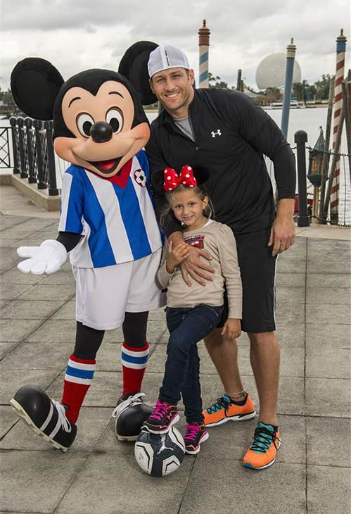 Juan Pablo Galavis, star of the 18th season edition of ABC's 'The Bachelor' (premieres on Jan. 5, 2014), poses with his daughter, Camila Valentina, and a soccer-clad Mickey Mouse at Walt Disney World in Lake Buena Vista, Florida on Dec. 29, 2013.