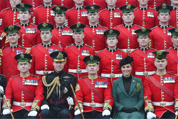 "<div class=""meta image-caption""><div class=""origin-logo origin-image ""><span></span></div><span class=""caption-text"">The time Kate Middleton posed with her husband Prince William (second from the left) for this photo. They are seen sitting among a group of 1st Battalion Irish Guards in Aldershot in the UK on March 17, 2013 -- St. Patrick's Day.  (Barcroft Media / Startraksphoto.com)</span></div>"
