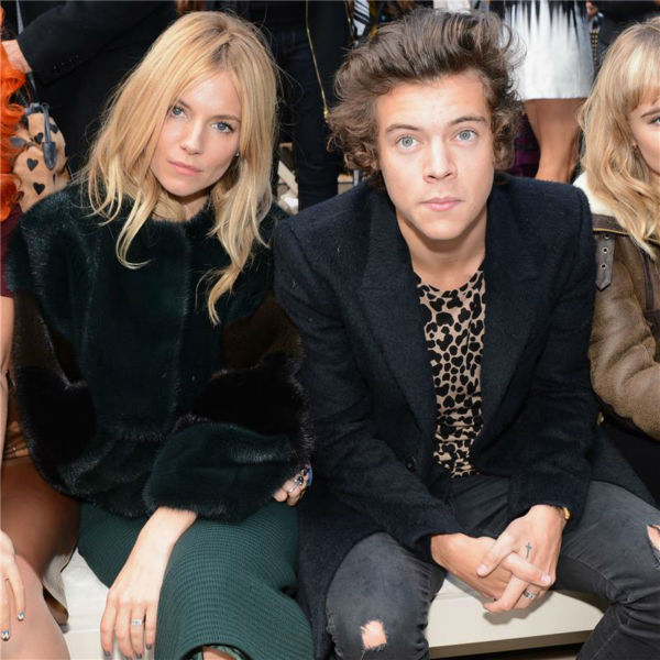 One Direction singer Harry Styles watches the Burberry Prorsum Spring / Summer 2014 fashion show with Sienna Miller during London Fashion Week fashion show on Sept. 16, 2013.