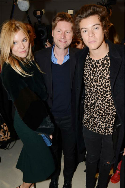 One Direction singer Harry Styles appears at the Burberry Prorsum Spring / Summer 2014 fashion show with Sienna Miller and Christopher Bailey, Burberry's chief creative officer, during London Fashion Week fashion show on Sept. 16, 2013.