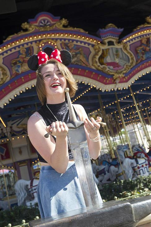 Maisie Williams, who plays Arya Stark on the HBO series 'Game of Thrones,' tries to pull the sword from the stone at the Magic Kingdom Park at the Walt Disney World Resort in Lake Buena Vista, Florida on Aug. 29, 2013.