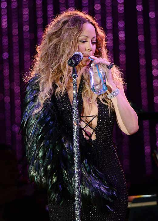 Mariah Carey, wearing a fancy sling, drinks a Fiji water handed to her by an assistant as she performs with the New York Philharmonic at the 2013 MLB All-Star Charity Concert, benefiting Hurricane Sandy relief efforts, in New York City&#39;s Central Park on July 13, 2013. She had recently suffered a shoulder injury during a music video shoot and had told her Twitter followers she would wear &#39;fashionable slings&#39; for the next two weeks. <span class=meta>(Humberto Carreno &#47; startraksphoto.com)</span>