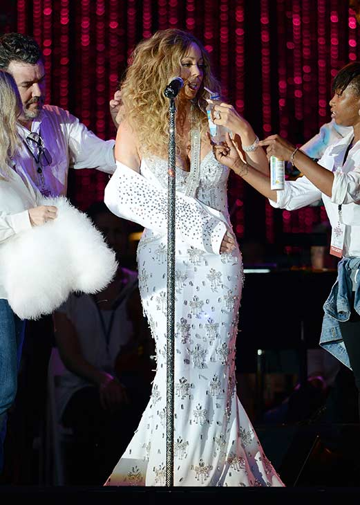 Mariah Carey, wearing a fancy sling, is helped by assistants as she performs with the New York Philharmonic at the 2013 MLB All-Star Charity Concert, benefiting Hurricane Sandy relief efforts, in New York City&#39;s Central Park on July 13, 2013. She had recently suffered a shoulder injury during a music video shoot and had told her Twitter followers she would wear &#39;fashionable slings&#39; for the next two weeks. <span class=meta>(Humberto Carreno &#47; startraksphoto.com)</span>