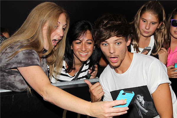 One Direction member Louis Tomlinson poses for a photo with a fan at the premiere of &#39;One Direction: This Is Us&#39; in New York on Aug. 26, 2013. <span class=meta>(Dave Allocca &#47; Startraksphoto.com)</span>