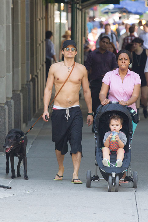 A shirtless Orlando Bloom takes a walk in New York City with his and Miranda Kerr's son, Flynn, his nanny and the family dog, Sidi, on July 16, 2013.