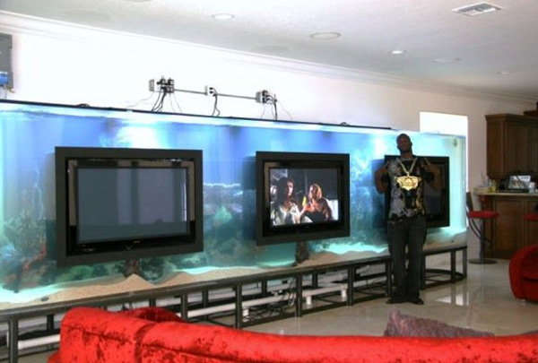 Chad Ochocinco's TV room contains an oversized fish tank by Acrylic Tank Manufacturing. Three flat screen televisions hang in front.