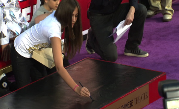 Paris Jackson writes 'Michael [heart] Jackson] on cement at her father's hand and footprint ceremony at the Grauman's Chinese Theatre on Jan. 26, 2012.