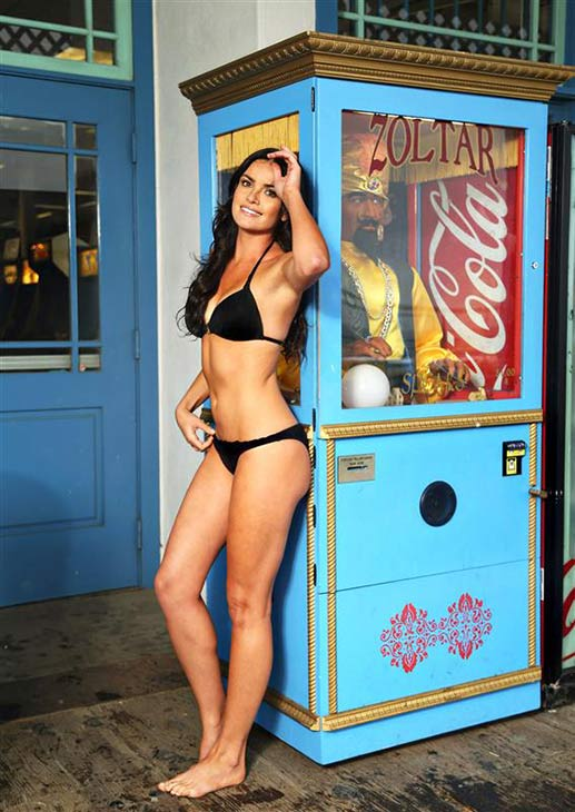 Former 'Bachelor' star Courtney Robertson poses in a bikini near a Zoltar fortune teller machine on the Santa Monica Pier in Santa Monica, California on Oct. 9, 2013.