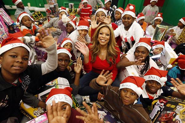 Talk show host Wendy Williams hands out Christmas presents to about 70 children at the daycare program of the Police Athletic League in Far Rockaway in New York on Dec. 13, 2013.