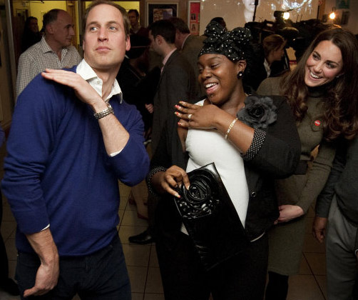 Prince William dances with Vanessa Boateng as his wife, Kate, the Duchess of Cambridge, looks on during their visit to Centrepoint's Camberwell Foyer in London on Dec. 21, 2011.