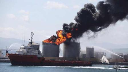Flames and smoke billow from an oil tank in the docks of Gibraltar, Tuesday May 31, 2011. The cause of the explosion was not immediately known but two people were reported injured. (AP Photo/Alicia Jimenez)