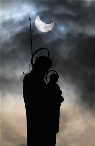A partial solar eclipse is seen through clouds over a church statue of the Virgin Mary, at the southern village of Maghdouche, Lebanon, on Tuesday, Jan. 4, 2011. A partial solar eclipse began Tuesday in the skies over the Mideast and will extend across much of Europe. &#40;AP Photo&#47;Mohammed Zaatari&#41; <span class=meta>(AP Photo&#47; Mohammed Zaatari)</span>