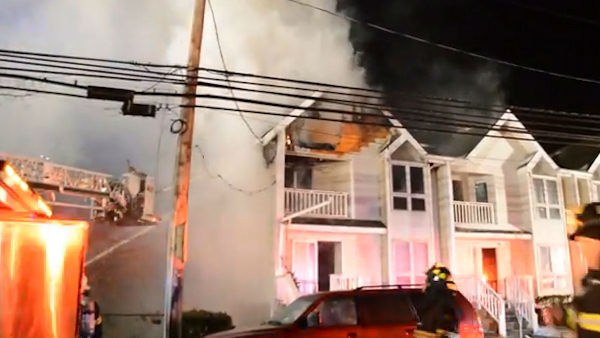 A 4-alarm fire burned through two condos in Albertson.  LIRR service was disrupted and power was cut to the area while firefighters worked. <span class=meta>(WABC Photo)</span>