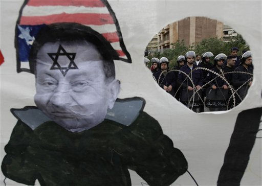 "<div class=""meta ""><span class=""caption-text "">Lebanese riot policemen, right, are seen through a hole in a banner depicting Egyptian President Hosni Mubarak wearing a US hat,  during a demonstration held by leftists protesters outside the Egyptian embassy in Beirut, Lebanon, on Saturday Jan. 29, 2011.  Demonstrators gathered in Beirut to show solidarity with protestors in Egypt.  (AP Photo/Hussein Malla) (AP Photo/ Hussein Malla)</span></div>"