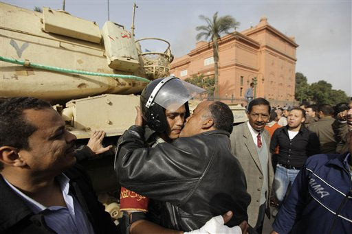 An Egyptian anti-government activist kisses an Egyptian army officer, center back, in Tahrir square in Cairo, Egypt, Saturday, Jan. 29, 2011.  &#40;AP Photo&#47;Ben Curtis&#41; <span class=meta>(AP Photo&#47; Ben Curtis)</span>
