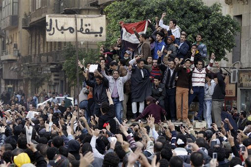 Egyptian anti-government protesters climb atop an Egyptian army armored personnel carrier, next to a signpost bearing the words &#34;Down Mubarak&#34;, in Cairo, Egypt, Saturday, Jan. 29, 2011. &#40;AP Photo&#47;Ben Curtis&#41; <span class=meta>(AP Photo&#47; Ben Curtis)</span>