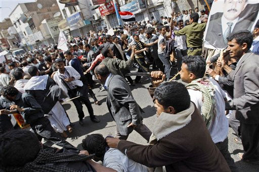 Supporters of the Yemeni government, right, reach to scuffle with anti-government demonstrators celebrating the resignation of Egyptian leader Hosni Mubarak and demanding the ouster of their own president, in Sanaa, Yemen, Saturday, Feb. 12, 2011. Yemeni police with clubs on Saturday beat anti-government protesters who were celebrating the resignation of Egyptian leader Hosni Mubarak and demanding the ouster of their own president. &#40;AP Photo&#47;Hani Mohammed&#41; <span class=meta>(AP Photo&#47; Hani Mohammed)</span>
