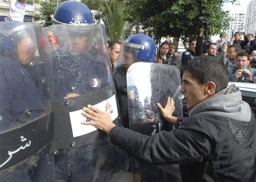 Protesters face with riot police officers during a protest in Algiers, Saturday, Feb. 19, 2011.  Algerian police thwarted a rally by some thousands of pro-democracy supporters Saturday, breaking up the crowd into isolated groups in a bid to keep them from marching. Police brandishing clubs, but no firearms, made their way through the crowd in central Algiers, banging their shields, tackling some protesters and keeping traffic flowing through the planned march route. &#40;AP Photo&#47;Sidali  Djarboub&#41;&#40;AP Photo&#47;Sidali  Djarboub&#41; <span class=meta>(AP Photo&#47; Sidali  Djarboub)</span>