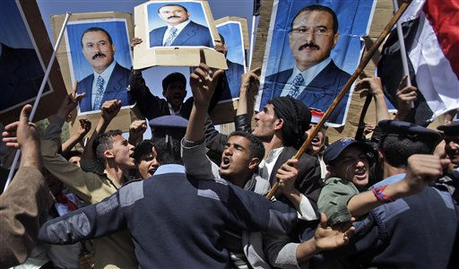 Yemeni policemen push back government supporters raising posters showing President Ali Abdullah Saleh, as they shout at anti-government demonstrators, not pictured, in Sanaa, Yemen, Sunday, Feb. 20, 2011. Some 3,000 students protesting at Sanaa University in the Yemeni capital seek to oust longtime President Ali Abdullah Saleh, a key U.S. ally in the fight against al-Qaida, and have been inspired by uprisings in Egypt and Tunisia. &#40;AP Photo&#47;Muhammed Muheisen&#41; <span class=meta>(AP Photo&#47; Muhammed Muheisen)</span>