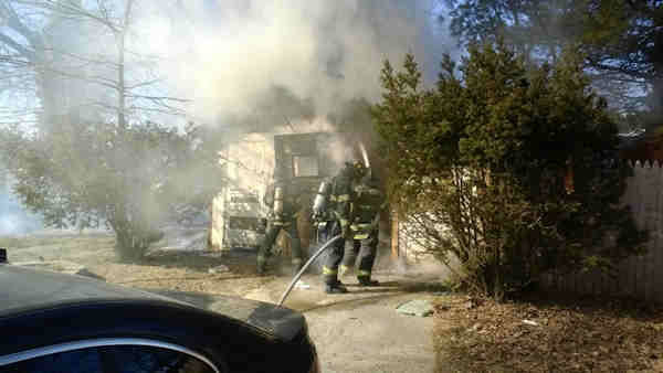 Up to a dozen pit bulls died in a raging fire in a garage behind a home in Freeport, Long Island.