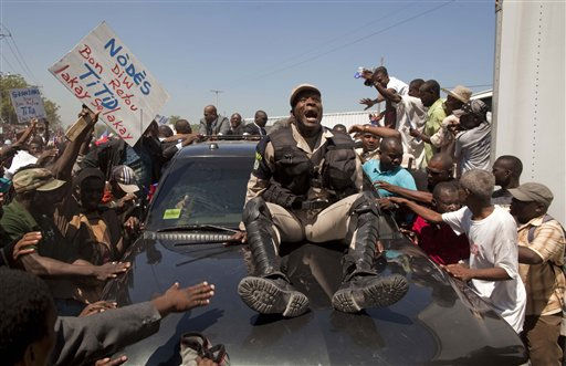 "<div class=""meta ""><span class=""caption-text "">A police officer rides on the hood of the vehicle carrying Haiti's former President Jean-Bertrand Aristide as he arrives to his home in Port-au-Prince, Haiti, Friday March 18, 2011. Aristide, who was forced to flee Haiti due to a rebellion in 2004 aboard a U.S. plane, returned after seven years of exile in South Africa, days before Haiti's presidential runoff election Sunday.  (AP Photo/Ramon Espinosa) (AP Photo/ Ramon Espinosa)</span></div>"