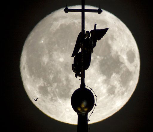 The city landmark, weathercock in the form of Angel fixed atop a spire of the Saints Peter and Paul Cathedral, is silhouetted on the setting moon in St.Petersburg, Russia, early Saturday, March 19, 2011. The world will see a super moon on March 19, and the full moon will make the sight even more interesting. The moon will pass the Earth at the distance of 365,600 kilometers, the closest in the past 19 years. &#40;AP Photo&#47;Dmitry Lovetsky&#41; <span class=meta>(AP Photo&#47; Dmitry Lovetsky)</span>