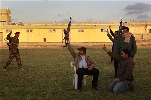 "<div class=""meta ""><span class=""caption-text "">Libyan government soldiers wave at foreign journalists at Moammar Gadhafi's Bab Al Azizia compound in  in Tripoli, Libya, Saturday March 19, 2011. President Barack Obama authorized limited military action against Libya Saturday, saying Moammar Gadhafi's continued assault on his own people left the U.S. and its international partners with no other choice. The Pentagon said 112 cruise missiles were launched from US and UK ships and subs, hitting 20 targets.  (AP Photo/Jerome Delay) (AP Photo/ Jerome Delay)</span></div>"
