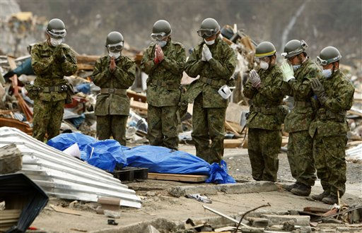 Members of Japan Self-Defense Force pray for the body of a tsunami victim wrapped in a tarp in Onagawa, Miyagi Prefecture, Japan, Sunday, March 20, 2011. &#40;AP Photo&#47;Shuji Kajiyama&#41; <span class=meta>(AP Photo&#47; Shuji Kajiyama)</span>