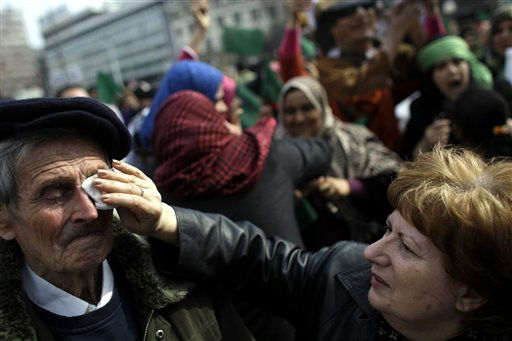 A woman wipes tears off her friend&#39;s eyes as they attend a protest to support Moammar Gadhafi in Belgrade, Serbia, Saturday, March 26, 2011. Several dozen people gathered in Belgrade&#39;s main square to show support for the Libyan leader. &#40;AP Photo&#47; Marko Drobnjakovic&#41; <span class=meta>(AP Photo&#47; Marko Drobnjakovic)</span>