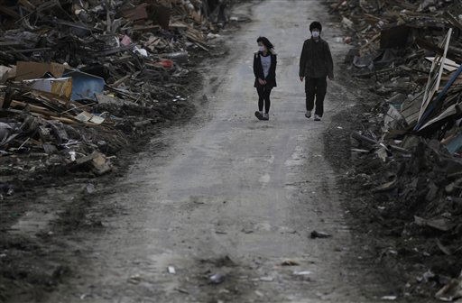 A couple walk through the rubble at the March 11 earthquake and tsunami devastated area in Kesennuma, Miyagi Prefecture, northern Japan, Saturday, April 2, 2011. &#40;AP Photo&#47;Eugene Hoshiko&#41; <span class=meta>(AP Photo&#47; Eugene Hoshiko)</span>