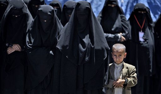 A Yemeni boy, right, looks on while praying with female anti-government protestors during a demonstration demanding the resignation of Yemeni President Ali Abdullah Saleh, in Sanaa, Yemen, Monday, April 4, 2011. Yemeni troops opened fire on crowds of protesters demanding the ouster of President Ali Abdullah Saleh, killing six and wounding more than 30 on Monday in the second straight day of clashes in a southern city, witnesses and medical officials said. The bloodshed in the city of Taiz further stoked the more than month-old uprising against Saleh&#39;s 32-year-rule. The opposition has been holding continual protest camps in main squares of cities around the country, and on Monday new demonstrations in solidarity with the Taiz protesters erupted in several places. &#40;AP Photo&#47;Muhammed Muheisen&#41; <span class=meta>(AP Photo&#47; Muhammed Muheisen)</span>
