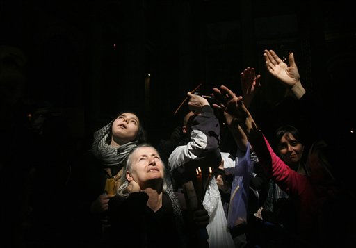 "<div class=""meta ""><span class=""caption-text "">Christian Orthodox pilgrims gesture towards a ray of light after the Holy Fire ceremony at the Church of the Holy Sepulcher in Jerusalem's Old City, Saturday, April 23, 2011. Orthodox Christians believe Jesus was crucified and buried at the site where the Church of the Holy Sepulcher now stands, and that a flame appears spontaneously from his tomb on the day before Easter to show he has not forgotten his followers. (AP Photo/Maya Hasson) (AP Photo/ Maya Hasson)</span></div>"