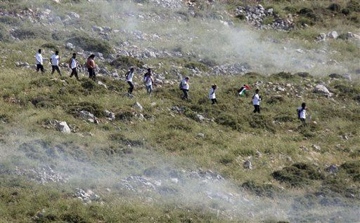 Palestinians run through tear gas fired by Israeli soldiers, during a demonstration against Jewish settlements in the northern West Bank village of Iraq Burin, near Nablus, Saturday, May 21, 2011. &#40;AP Photo&#47;Nasser Ishtayeh&#41; <span class=meta>(AP Photo&#47; Nasser Ishtayeh)</span>