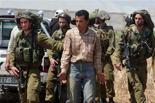Israeli soldiers detain a Palestinian man after they destroy wells used by Palestinian farmers for agricultural irrigation near the West Bank village of Kfar Dan west of Jenin, Sunday, May 29, 2011. The Israeli military says the wells were drilled illegally and endanger an underground aquifer. &#40;AP Photo&#47;Mohammed Ballas&#41; <span class=meta>(AP Photo&#47; Mohammed Ballas)</span>