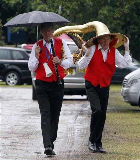 Members of a jazz band, prepare to entertain the crowd take shelter as heavy rain falls on the fifth day of the Royal Ascot horse race meeting at Ascot, England, Saturday, June, 18, 2011.  Ascot is celebrating 300-years of horse racing at the Royal Racecourse, that began with Britain&#39;s Queen Anne spotting an open heath suitable for racing, the first race run in August 1711, and today the Ascot horse race meeting attracts people who don their finest clothing and rainy weather doesn&#39;t seem to dampen their enthusiasm.  &#40;AP Photo&#47;Alastair Grant&#41; <span class=meta>(AP Photo&#47; Alastair Grant)</span>
