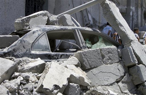 In this photo taken on a government-organized tour, a damaged car lies underneath rubble opposite a damaged residential building in Tripoli, Libya, Sunday, June 19, 2011. The Libyan government accused NATO of bombing a residential neighborhood in the capital and killing civilians early Sunday, adding to its charges that the alliance is striking nonmilitary targets. &#40;AP Photo&#47;Adam Schreck&#41; <span class=meta>(AP Photo&#47; Adam Schreck)</span>