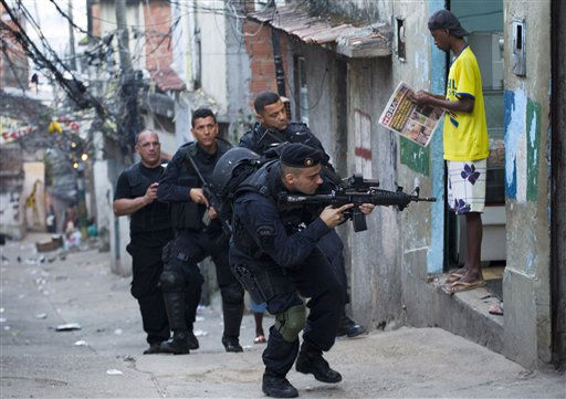 A man reads a newspaperas members of Brazil&#39;s special police unit BOPE take positions during a raid of the Mangueira slum in Rio de Janeiro, Brazil, Sunday June 19, 2011. Hundreds of police officers and troops backed by helicopters and several armored vehicles invaded the shantytown early Sunday. They took control of the slum in what is the first step before installing police units to help pacify the poor community. Police did not face any resistance from drug trafficking gangs in the raid to help bring peace near Maracana stadium ahead of the 2014 World Cup and the 2016 Olympics.  &#40;AP Photo&#47;Victor R. Caivano&#41; <span class=meta>(AP Photo&#47; Victor R. Caivano)</span>