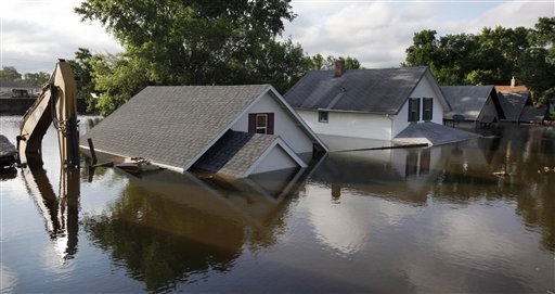 "<div class=""meta ""><span class=""caption-text "">Floodwaters from the Souris River surround homes and a back hoe on 3rd St. N.W.  near Minot State University Monday, June 27, 2011 in Minot, N.D. As the river hit its record-shattering peak and began a slow retreat, residents looked ahead to an arduous rebuilding job while continuing to deal with short-term obstacles such as sharing the homes of friends and relatives, traffic tie-ups and an advisory to boil drinking water.  (AP Photo/Charles Rex Arbogast) (AP Photo/ Charles Rex Arbogast)</span></div>"